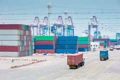 Busy container terminal closeup. Trucks in transshipment area Stock Photography