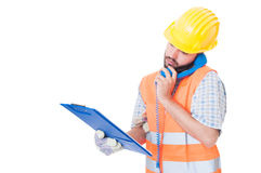 Busy contractor using phone while holding clipboard Royalty Free Stock Images