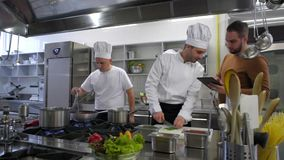 Chef cooking and manager with tablet consulting