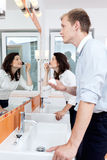Busy couple in a bathroom Stock Images