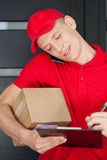 Busy courier calling on mobile phone. And writing on clipboard Stock Photography