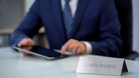 Busy credit analyst working on tablet pc, checking financial report online, work. Stock photo royalty free stock photos