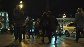 Busy crowded night city pedestrians sidewalk, road traffic. Couples and families walking. Slowmotion stock video footage