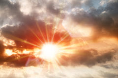 busy dark cloud over vibrant color sky with red sunstar flare Stock Images