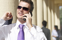 Busy day. Young businessman on the go, talking on the phone stock image