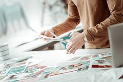 Designer from a fashion studio cutting the pictures for a new catalogue. Busy day. Designer from a fashion studio wearing a brown garment cutting the pictures royalty free stock photography
