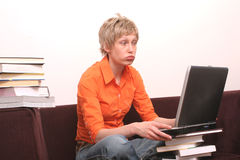Busy day - problems. Busy woman working on laptop with a lot o books around stock photos