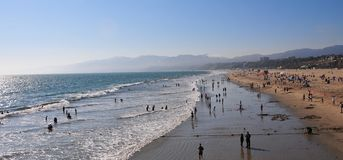 Santa Monica Beach in California. Busy day at Santa Monica Beach. View of the water with people walking, swimming and playing. Family fun. Sand, waves, sunlight Royalty Free Stock Image