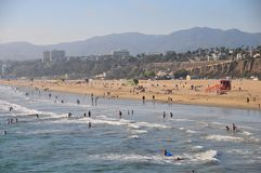 Santa Monica Beach in California. Busy day at Santa Monica Beach. View of the water with people walking, swimming and playing. Family fun. Sand, waves, sunlight Stock Photos