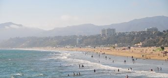 Santa Monica Beach in California. Busy day at Santa Monica Beach. View of the water with people walking, swimming and playing. Family fun. Sand, waves, sunlight Royalty Free Stock Photo