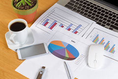 Busy desktop with financial data print outs and technology Royalty Free Stock Photo