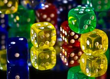Busy Dice. Colored dice on mirror surface Stock Photo