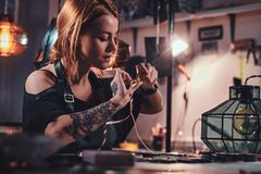 Attractive woman is working at creative glass workshop stock photography
