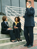 Busy Diversity Business People. Group of business people, caucasian and african american are talking outdoor by stair Royalty Free Stock Photo