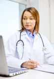 Busy doctor with laptop computer and clipboard Royalty Free Stock Photo