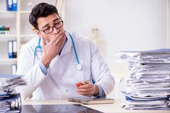 The busy doctor with too much work in hospital. Busy doctor with too much work in hospital Royalty Free Stock Photo