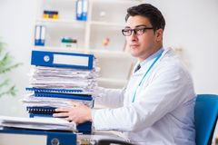 The busy doctor with too much work in hospital. Busy doctor with too much work in hospital Stock Photography