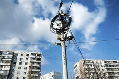 Busy electricity line and security camera against blue sky. Royalty Free Stock Photography