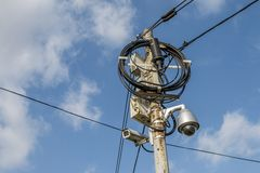 Busy electricity line and security camera against blue sky. Stock Photos