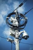 Busy electricity line and security camera against blue sky. Stock Photo
