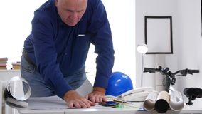 Busy Engineer Examine a Construction Plan Thinking Calm and Making Calculations