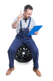 Busy engineer on garage writing on clipboard Royalty Free Stock Photo