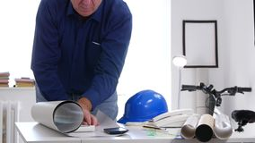 Busy engineer in interior office open and analyze a building plan on the desk.  stock video footage