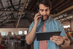 Busy entrepreneur using his tablet while talking on a cellphone. Close up of young craftsman with a beard talking on a cellphone and using a digital tablet while Stock Image