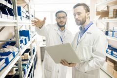 Busy factory lab technicians keeping records of devices. Serious concentrated handsome male multiethnic engineers discussing quality of devices while using Stock Images