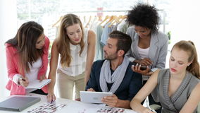 Busy fashion design team working together at table stock footage