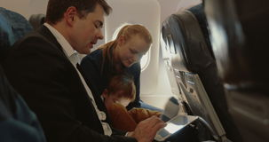 Busy father, child and mother traveling by plane. Young family of three traveling by air. Father busy with touch pad and talking to the wife, child using smart stock footage
