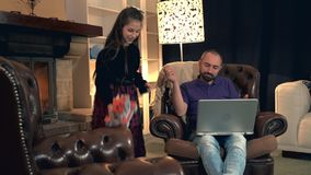 Busy father giving his daughter smartphone instead of playing together. Dad working on computer and doesn't have time to pay his little girl attention stock footage