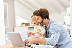 Busy father holding baby and working on laptop Stock Photography