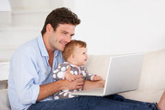 Busy father working on laptop. With infant Royalty Free Stock Photo