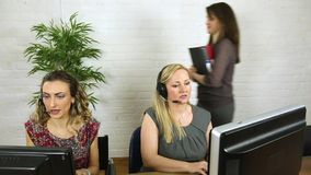 Busy female customer service office staff talking to clients in busy offic be stock video footage