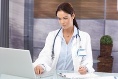 Busy female doctor in office Stock Images