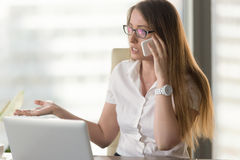 Busy female entrepreneur arguing by phone Stock Images