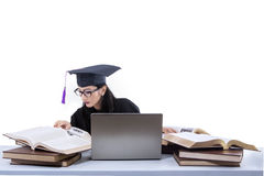 Busy female graduate reading books - isolated Stock Images