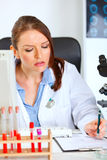 Busy female medical doctor working at her office Stock Image