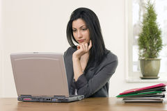 Busy female in office. Attractive young female busy in office working on laptop, horizontal composition with text space Royalty Free Stock Image