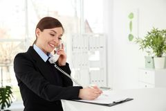 Busy female receptionist at workplace. In hotel royalty free stock photography