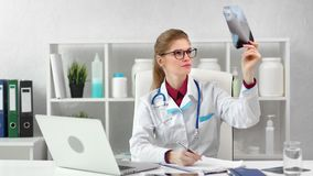 Busy female surgeon checking x-ray image taking note working at modern clinic room