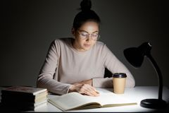Busy female teenager reads book, uses table lamp, prepares for final examination, sits at desktop, wears optical round glasses, po. Ses against dark background stock photo