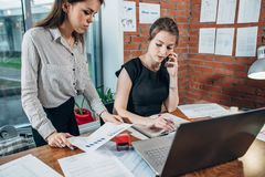 Busy female top manager talking on the phone while her assistant showing her financial statistics Royalty Free Stock Photo