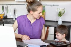 Busy female and young mother makes financial report, works with documents and modern laptop computer, has talk with her small son stock photos