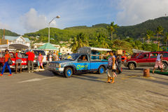 A busy ferry wharf in the caribbean. Disembarking passengers and vehicles congregated on the dock after the arrival of the inter-island ferry at bequia stock photography