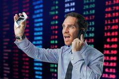Busy financial broker. On the background of electronic stock exchange board stock image