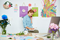 Busy florist in lovely studio. Blond-haired florist in denim shirt sitting on stepladder, talking to her client on smartphone and taking notes with pencil Stock Photo