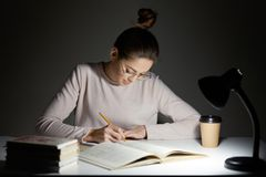 Busy freelancer rewrites infrormation into notepad, prepares article for publication, reads books, writes some notes in organizer,. Drinks takeaway coffee, sits royalty free stock photo