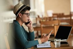 Freelancer busy with work. Busy freelancer taking orders by phone and by messanger stock image